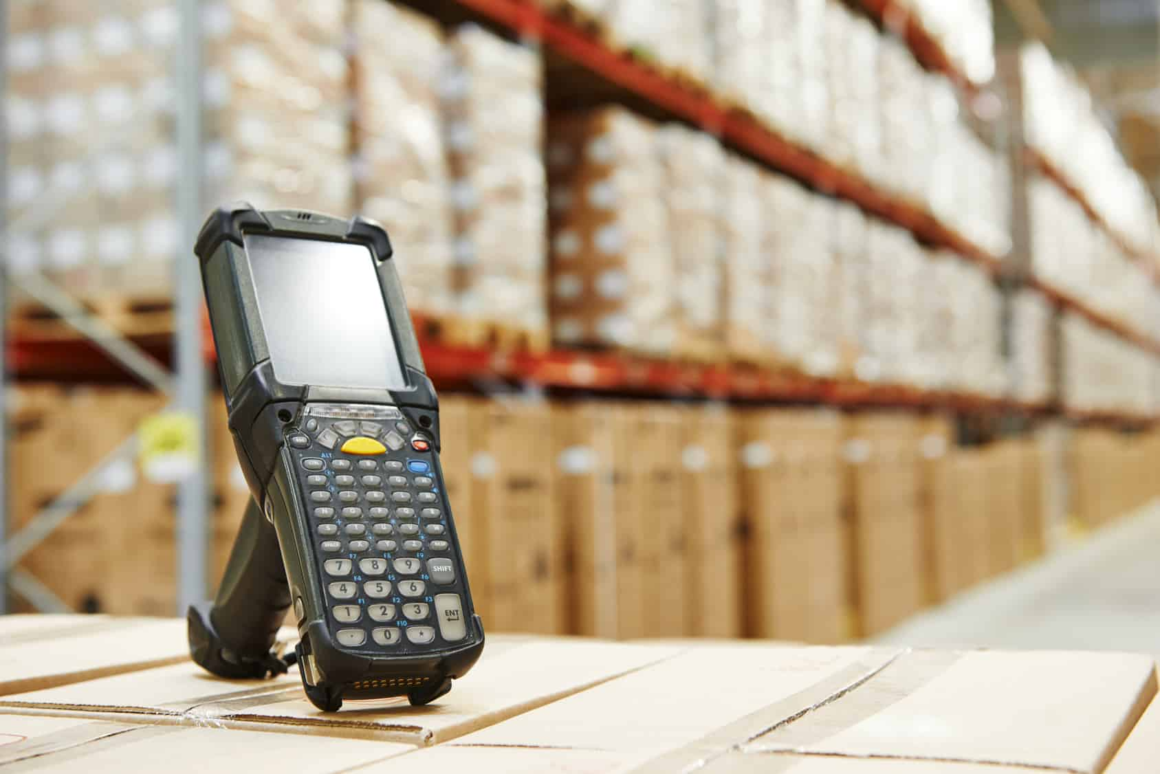 A hand scanner being used in a warehouse.